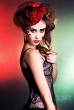 Young attractive woman with beautiful makeup in green and red colors in the red hat at the masquerade Royalty Free Stock Image