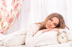 Young attractive woman in bed with alarm clock Stock Images