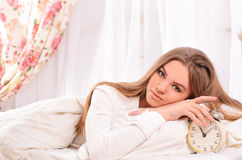 Young attractive woman in bed with alarm clock Royalty Free Stock Image