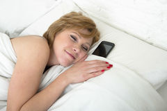 Young attractive woman in bed alone with mobile phone as sleeping partner in internet and smart phone addiction concept Royalty Free Stock Photography