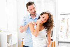 Young attractive woman being manipulated by physiotherapist royalty free stock photos