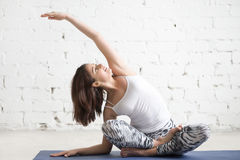 Young attractive woman in bending Sukhasana pose, white studio Stock Images