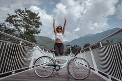 Young attractive woman with bicycle on a bridge stock images