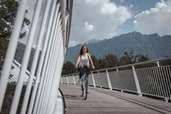 Young attractive woman with bicycle on a bridge stock photography