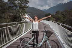 Young attractive woman with bicycle on a bridge stock image