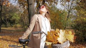 Young female with bicycle. Young attractive woman with bicycle posing in autumn park in beautiful sunny day stock footage