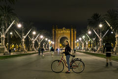 Young and attractive woman on bicycle is standing in front of Arc de Triomf Stock Photo