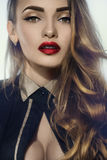 Young attractive woman with big breast and red lips. Close up portrait of young attractive woman with big breast and red lips looking at the camera in studio on Royalty Free Stock Photography