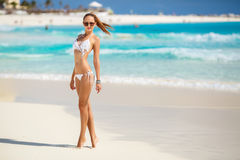 The young attractive woman in bikini on a beach Royalty Free Stock Photos