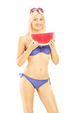 Young attractive woman in bikini holding a slice of watermelon Royalty Free Stock Photography