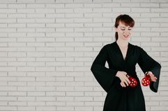 a young attractive woman in black dress, dancing with red castanets, smiling, white wall background royalty free stock image