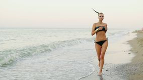 Young attractive woman in black leather swimsuit running by the sea on the beach. Her ponytail is waving in the wind stock video footage