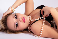 Young attractive woman in black lingerie and a pearl necklace Royalty Free Stock Photos