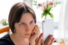 Young attractive woman in black t-short is sitting near the window with her electronic device and looking at display. Young attractive woman in black t-short is stock image