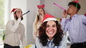 Young attractive woman blowing golden confetti from hands wearing christmas hat while her co-workers partying in the. Background in the office celebrating stock video footage
