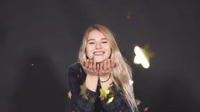 Young attractive woman blowing golden confetti from hands. Slow motion. Young attractive woman blowing golden confetti from hands stock video