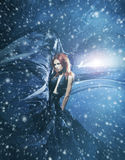 Young attractive woman in blowing silk on a smoky background. Young attractive woman in a blowing sil. Snowy background with wind, lighting and blizzard Royalty Free Stock Photos