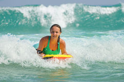 Young attractive woman bodyboards on surfboard with nice smile Royalty Free Stock Photo