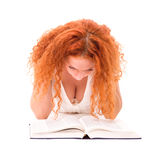 Young attractive woman with the book lying Stock Photography