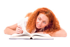 Young attractive woman with the book lying Royalty Free Stock Images