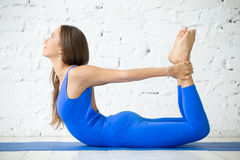 Young attractive woman in Bow pose, white studio background Royalty Free Stock Images