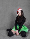 Young attractive woman in a bright green skirt and Christmas hat Royalty Free Stock Photos