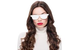 Young attractive woman with bright makeup wearing white sunglasses and raising brow,. Isolated on white stock photography