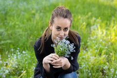 Young attractive woman brought a bouquet of forget-me-nots to her face royalty free stock photography