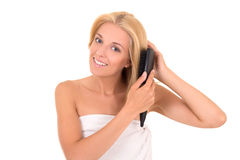 Young attractive woman brushing her hair on white background Royalty Free Stock Photography