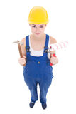 Young attractive woman builder in workwear with hammer and paint Stock Image