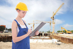 Young attractive woman builder writing something in clipboard Stock Image