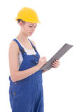 Young attractive woman builder writing something in clipboard is Stock Photos