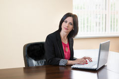 Young attractive woman in a business suit sitting at Desk with laptop Stock Image