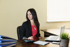 Young attractive woman in a business suit sitting at a Desk in the office Stock Photo