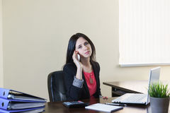 Young attractive woman in a business suit talking on phone at Desk in office Stock Images