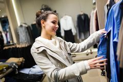 Young attractive woman buying clothes in mall. Young attractive woman buying clothes in shopping mall Stock Images