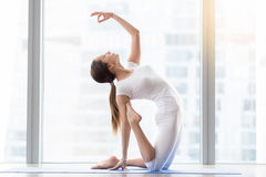 Young attractive woman in Camel pose with mudra, floor window Stock Image