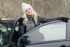 Young attractive woman with car keys in the hand. Concepts of purchasing or rental car: woman with car keys in the hand standing near the black car, winter Royalty Free Stock Images