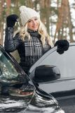 Young attractive woman with car keys in the hand. Concepts of purchasing or rental car: woman with car keys in the hand standing near the black car, winter Stock Photos