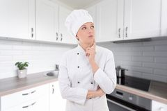 Young attractive woman chef dreaming in modern kitchen Royalty Free Stock Photos