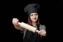 Young Attractive Woman Chef In Black Uniform Holds Rolling Pin On Black Background. Focus On Rolling Pin Royalty Free Stock Photo