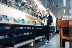 Young attractive woman choosing vinyl record in music record shop royalty free stock image
