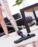 Young attractive woman is cleaning vacuum on carpet. Royalty Free Stock Photography