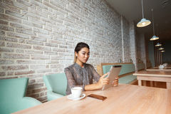 Young attractive woman concentrated reading electronic book on her digital tablet,. Asian female browsing website pages on touch pad while breakfast in modern Stock Images