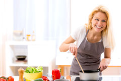 Young attractive woman cooking in a kitchen Stock Images