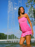 Young attractive woman cooling in the fountain Stock Photo