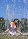 Young attractive woman cooling in the fountain royalty free stock image