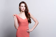 Young attractive woman in coral dress Stock Image