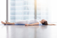 Young attractive woman in Corpse pose against floor window. Young woman practicing yoga, lying in Savasana exercise, Dead Body, Corpse pose, working out, wearing royalty free stock photography
