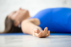 Young attractive woman in Corpse pose, white studio background. Young attractive woman practicing yoga, lying in Dead Body, Corpse exercise, Savasana pose Stock Photography